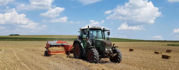 Traktor faehrt mit Strohpresse am Feld