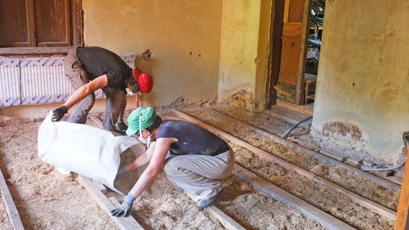 Zwei Personen daemmen den Boden mit Biostroh